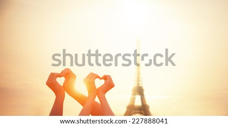 Two lovers showing heart shapes with hands and parisian Eiffel tower on background. - stock photo