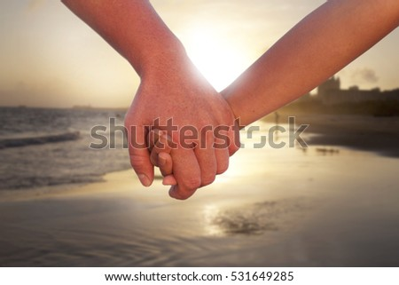 two lovers walking hand to hand on the beach at sunset time.