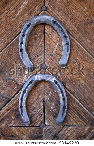 Two lucky horseshoes on wooden wall - stock photo