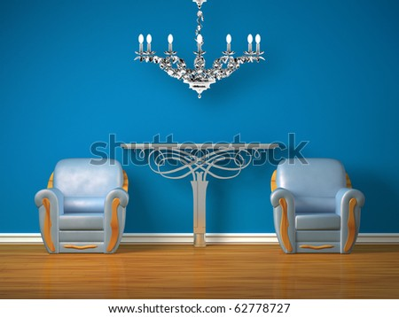Two luxurious chairs with metallic console and silver chandelier in minimalist interior - stock photo