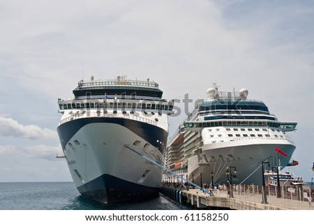 Two luxury cruise ships docked under a cloudy sky - stock photo