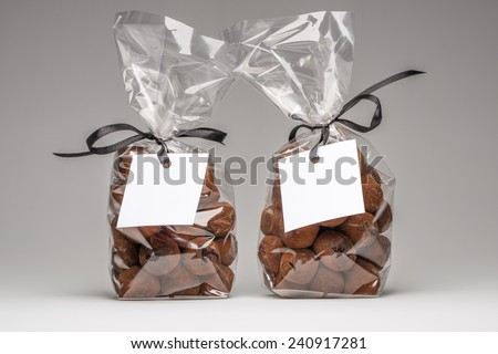Two luxury plastic bags with elegant black ribbons of chocolate truffles for Christmas gift. Blank label and copy space. Shooting on grey background in studio. - stock photo