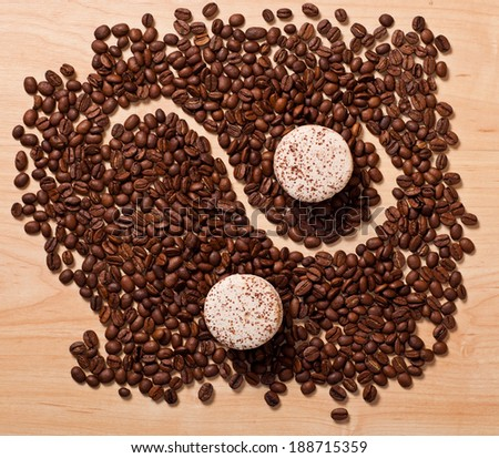 two macaroons on coffee beans background - stock photo