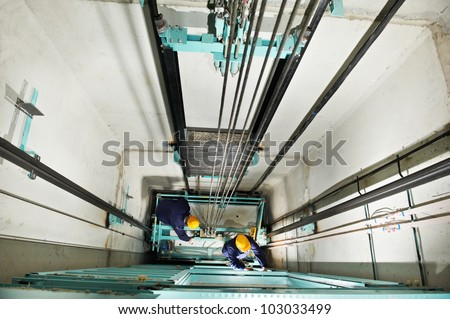 two machinist worker technicians at work adjusting lift with spanners in elevator hoistway - stock photo