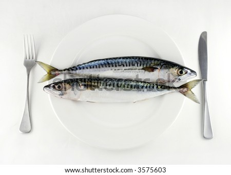 two mackerel on a white plate with knife and fork - stock photo