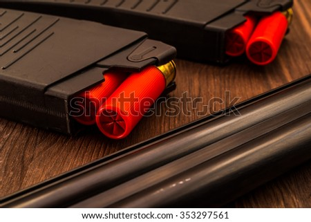 Two magazines with red cartridges 12 gauge and double-barreled shotgun on the wooden table. Close up view - stock photo