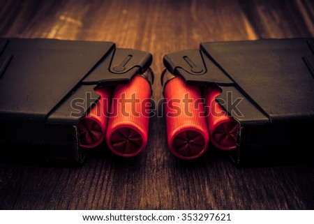 Two magazines with red cartridges 12 gauge lie opposite each other on the wooden table. Close up view, image vignetting and the yellow-blue toning - stock photo