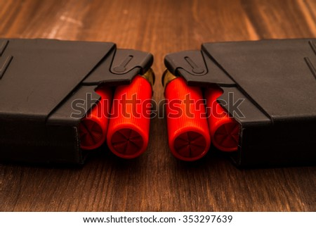 Two magazines with red cartridges 12 gauge lie opposite each other on the wooden table. Close up view - stock photo