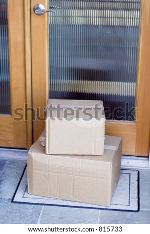 Two mail boxes that have been delivered to the front door. - stock photo