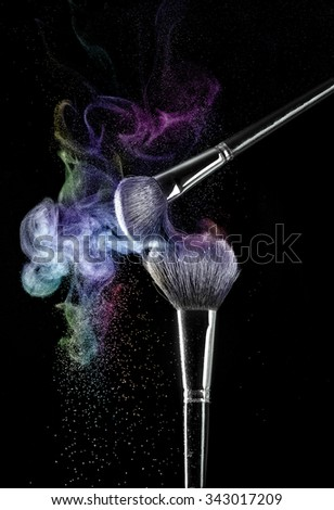 Two makeup brushes with powder on a black background