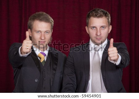 two male actors holding thumbs up on the stage - stock photo