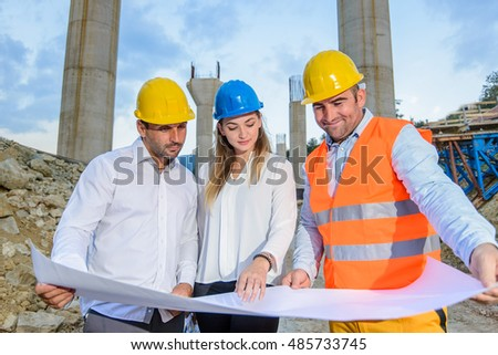 Two male and one female worker looking at a plan for the construction of the bridge and discuss the details