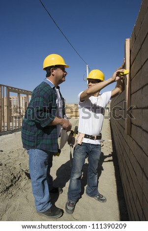 Two male architects examining brick wall at construction site - stock photo