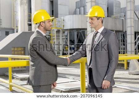 Two male architects shaking hands at construction site - stock photo