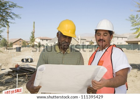 Two male architects with reading blueprint at construction site - stock photo
