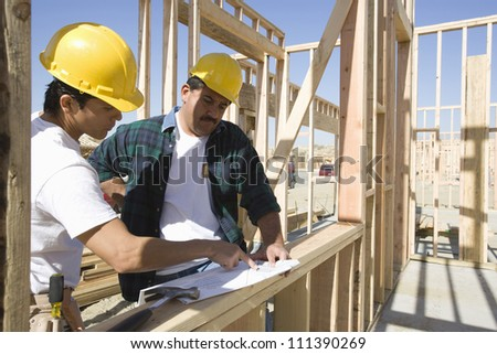 Two male architects working together at construction site with blueprint