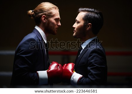 Two male business boxers looking at one another in isolation - stock photo