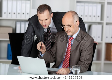 Two male business colleagues working together in an office discussing information on the screen of a laptop computer - stock photo