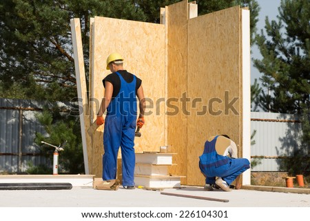 Two Male Construction Workers Busy in Building Real Estate House - stock photo