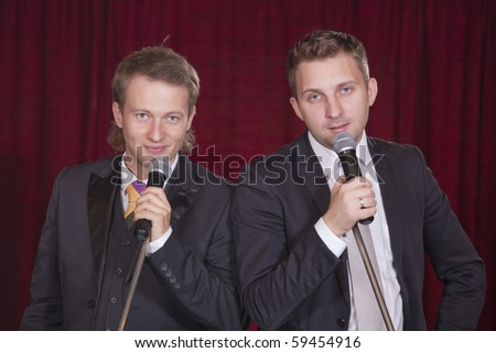 two male entertainers with microphones on the stage - stock photo