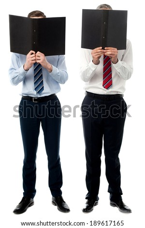 Two male executives hiding face behind a file folder - stock photo