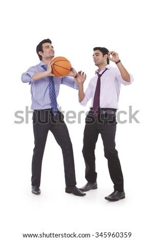 Two male executives playing basketball - stock photo