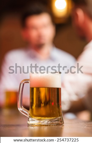 Two male friends in a pub with glasses of beer. Focus on a glass of beer. - stock photo