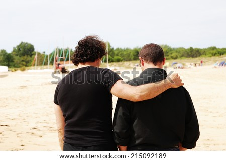 Two male friends in black clothes walking on the seaside with one of them hugging the other - stock photo