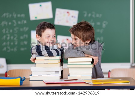 Two male friends studying with a pile of books on the table - stock photo