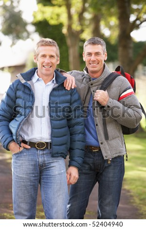Two Male Friends Walking Outdoors In Autumn Park Together - stock photo