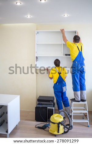 two male furniture adjusters in uniform hang wall drawer - stock photo