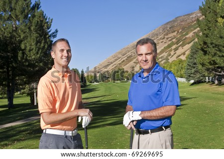 Two male golfers playing golf together - stock photo