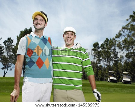 Two male golfers standing with arm around at golf course - stock photo