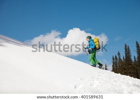 Two male hikers against blue sky in winter mountains passing away from camera. Concept of success living and free traveling, active leisure, health care and well being.