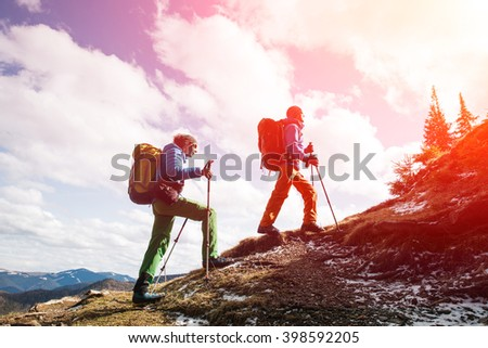 Two male hikers in winter mountains passing away from camera. Concept of success living and free traveling, active leisure, health care and well being.