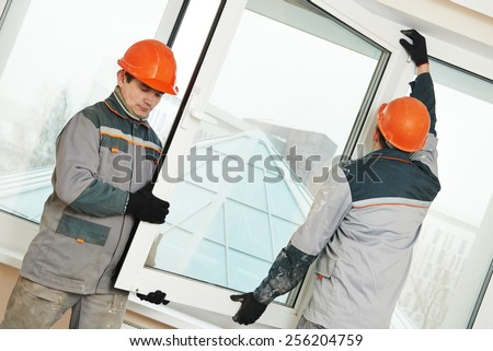 Two male industrial builders workers at window installation - stock photo