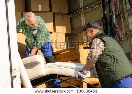 Two male movers putting furniture and boxes  in moving truck - stock photo