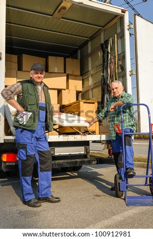Two male movers unload furniture and boxes  from moving truck - stock photo
