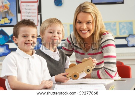 Two Male Primary School Pupils And Teacher Working At Desk In Classroom - stock photo