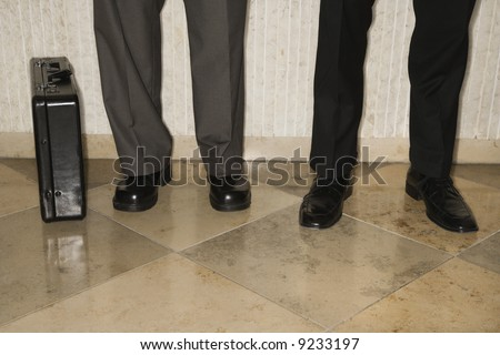 Two male's legs and briefcase - stock photo