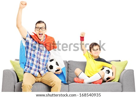 Two male sport fans sitting on a sofa and watching sport isolated on white background - stock photo
