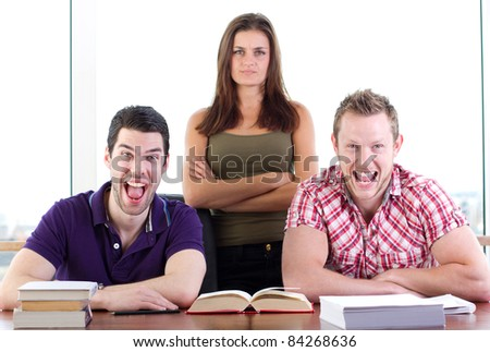 Two male students share a joke, the woman does not approve