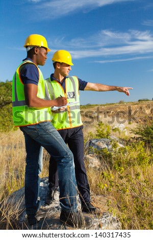 two male surveyors at work - stock photo