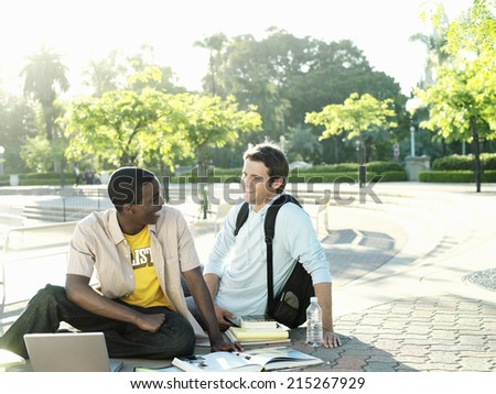 Two male university students sitting on ground with textbooks and laptop, smiling - stock photo