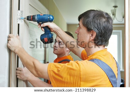 Two male workers carpenters at internal door installation  - stock photo