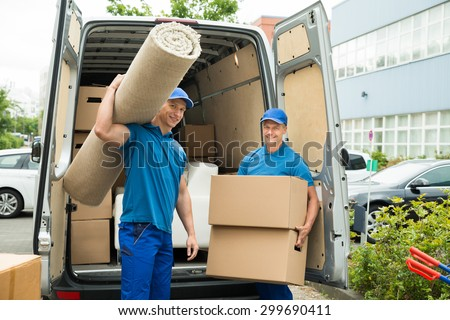 Two Male Workers Carrying Carpet And Cardboard Boxes In Front Of Van - stock photo
