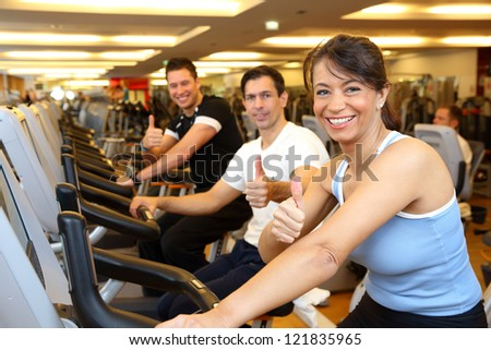 Two man and a woman on exercise bike smiling and giving thumbs up - stock photo