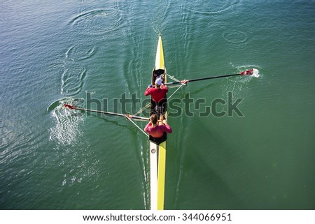 Two Man in a boat, rowing on the tranquil lake - stock photo