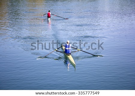 Two Man in a boats, rowing on the tranquil lake - stock photo