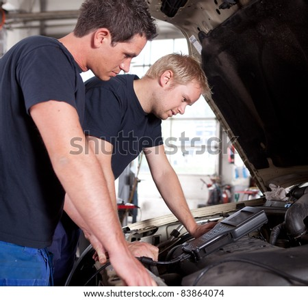 Two man mechanics looking a diagnostics equipment, servicing car - stock photo
